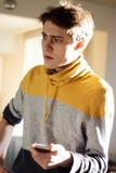 De kerel in de gele sweater is zeer overweldigd door het feit dat hij op de telefoon heeft stock fotografie