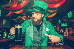 De kerel in groen kostuum zit bij lijst in bar en het stellen Hij houdt mok donker bier en kijkt op camera Hij is zeker royalty-vrije stock foto