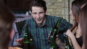 De kerel in het bedrijf van vrienden vertelt animatedly een interessant verhaal Het bedrijf drinkt bier in een restaurant stock videobeelden