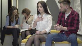 De kerel krijgt op de telefoon het nieuws waarvan het meisje bewustzijn verliest De jonge vrouw verzwakt in de werkplaats stock video