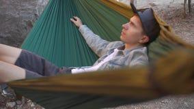 De kerel ligt op hangmat het slingeren stock video