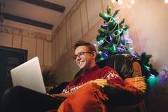 De kerel maakt een aankoop op Internet via een lapto royalty-vrije stock foto's
