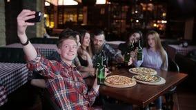 De kerel maakt een vriendenbedrijf in pizzeria Een bedrijf van vrienden die in pizzeria rusten en selfie op maken stock video