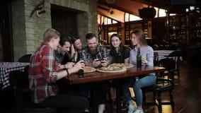 De kerel maakt een vriendenbedrijf in pizzeria Een bedrijf van vrienden die in pizzeria rusten en selfie op maken stock footage