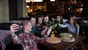 De kerel maakt een vriendenbedrijf in pizzeria Een bedrijf van vrienden die in pizzeria rusten en selfie op maken stock videobeelden