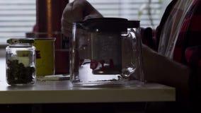 De kerel maakt gerolde sigaret bij lijst met grote mok en glastheepot in keuken stock videobeelden