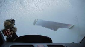 De kerel maakt venster schoon van een auto van binnenuit wordt geschoten die stock footage