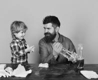 De kerel met baard en snor met rubberhandschoenen houdt nevel royalty-vrije stock foto