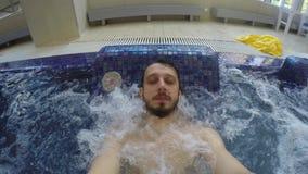 De kerel met de baard is in de pool met bellen stock videobeelden