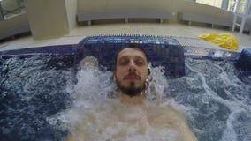 De kerel met de baard is in de pool met bellen stock video