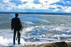 De kerel met de gitaar op het strand in het jasje, op ijs Royalty-vrije Stock Fotografie