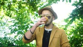 De kerel met een baard en in modieuze kledij drinkt koffie stock videobeelden
