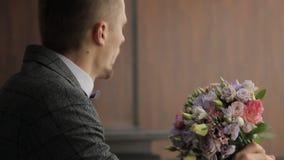 De kerel met een boeket van bloemen in zijn handen stock video