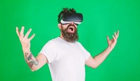 De kerel met hoofd opgezette vertoning werkt in VR op elkaar in Mens met baard in VR-glazen, groene achtergrond Machtsconcept Hip stock fotografie