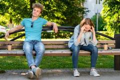 De kerel met meisje in de zomer op de bank Conflicten in een verhouding Het meisje heeft een sterke hoofdpijn Ruzies en royalty-vrije stock foto