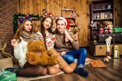 De kerel met twee meisjes in een ruimte met Kerstmisdecoratie royalty-vrije stock fotografie