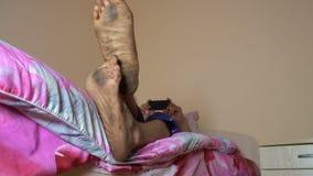 De kerel met vuile voeten ligt op het bed stock footage