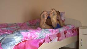 De kerel met vuile voeten ligt op het bed stock video