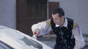 De kerel in nationaal kostuum houdt op schoonmakend de auto'svoorruit stock footage