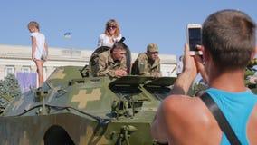 De kerel neemt beelden op androïde van militairen in militaire eenvormig en vrouw op openluchttank in stad stock videobeelden