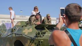 De kerel neemt beelden op androïde van militairen in militaire eenvormig en vrouw op openluchttank in stad stock video