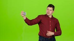 De kerel neemt beelden van zich, stelt en glimlacht Het groene scherm stock footage