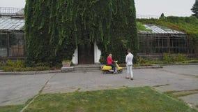De kerel neemt een beeld van een meisjeszitting op een autoped Geschoten op Hommel stock footage