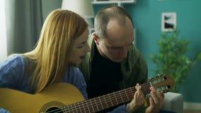 De kerel onderwijst meisje om gitaar in zijn woonkamer te spelen stock videobeelden