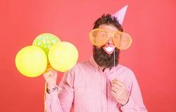 De kerel in partijhoed met luchtballons viert Hipster in het reuzezonnebril vieren Mens met baard op vrolijk gezicht stock foto