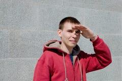 De kerel in rode hoodie en de tribunes bij de muur en dekking zijn ogen met zijn hand van de heldere zon royalty-vrije stock foto's