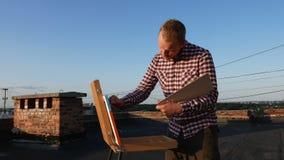 De kerel schildert een beeld Op het dak stock videobeelden
