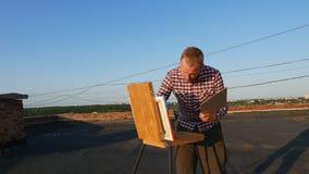 De kerel schildert een beeld Op het dak stock video