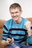 De kerel schreeuwt gelukkig, lettend op TV stock fotografie