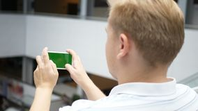 De kerel speelt het spel op smartphone in schutterschutter en ras Het groene telefoonscherm voor het sluiten Een mens in stock video