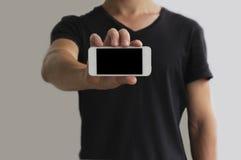 De kerel toont horizontaal een witte telefoon met het zwart scherm Stock Afbeelding