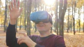 De kerel in virtuele werkelijkheidshoofdtelefoon speelt een spel op zonnige dag in het de herfstpark stock video