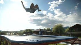 De kerel voert het acrobatische springen op een trampoline tegen een achtergrond van bergen en blauwe hemel uit stock videobeelden