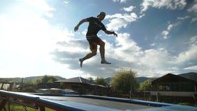 De kerel voert het acrobatische springen op een trampoline tegen een achtergrond van bergen en blauwe hemel uit stock footage