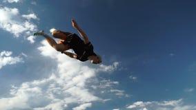 De kerel voert het acrobatische springen op een trampoline tegen een achtergrond van bergen en blauwe hemel uit stock video
