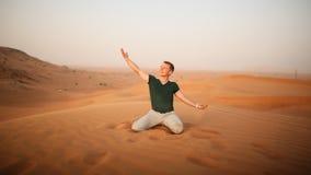 De kerel werpt zand over zich in de woestijn De woestijn is naast Doubai De V.A.E Royalty-vrije Stock Foto's