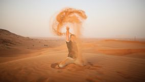 De kerel werpt zand over zich in de woestijn De woestijn is naast Doubai De V.A.E Royalty-vrije Stock Afbeelding