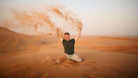 De kerel werpt zand over zich in de woestijn De woestijn is naast Doubai De V.A.E Royalty-vrije Stock Afbeeldingen