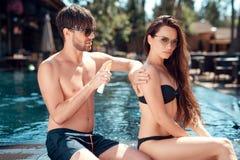 De kerel wrijft het meisje ` s terug met een zonnescherm dichtbij de pool royalty-vrije stock foto