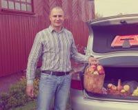 De kerel zet appelen in de boomstam van auto royalty-vrije stock foto