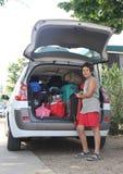 De kerel zet de zak in de bagage van de auto tijdens het vertrek Stock Foto's