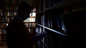 De kerel zet het boek in zijn plaats in de bibliotheek stock footage