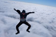 De kerel zit boven witte wolken stock afbeelding