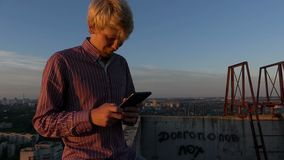 De kerel zit en bekijkt zijn mobiel op een hoge bouwwerf zonsondergang stock footage