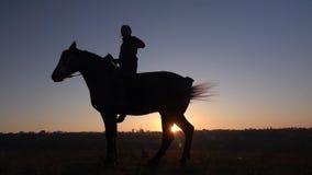 De kerel zit op een paard en geeft hem twee benen Langzame Motie Silhouet Zachte nadruk stock footage