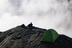 De kerel zit op de Preikestolen-klip, Noorwegen Stock Foto's